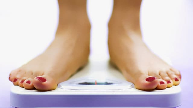 A woman checking her weight on a bathroom scale.